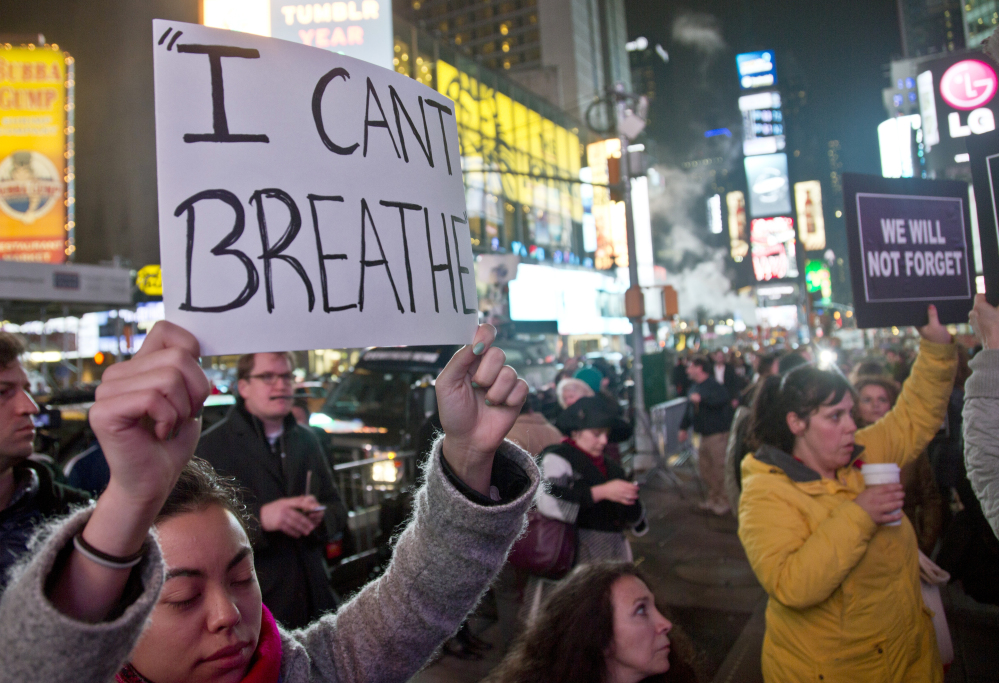 Protesters carry signs in Times Square on Wednesday evening in reaction to a grand jury's decision not to indict a police officer in the death of Eric Garner in New York.
