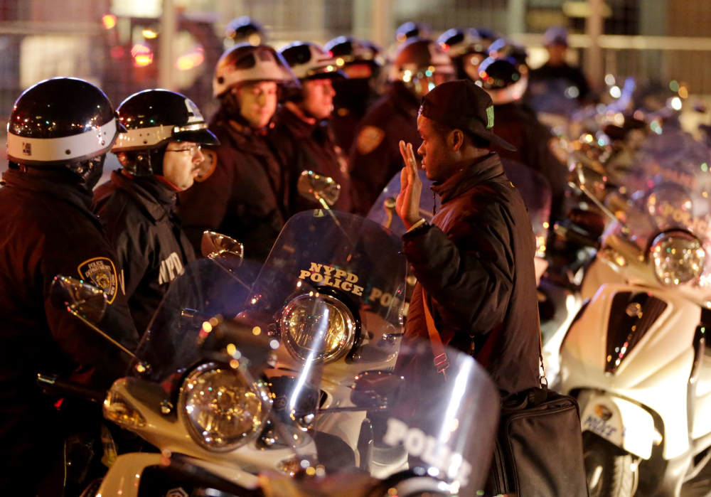 A protester stands in front of a line of police officers during a protest Wednesday night in New York after a grand jury decided not to indict a New York police officer who was involved in the death of an unarmed black man.