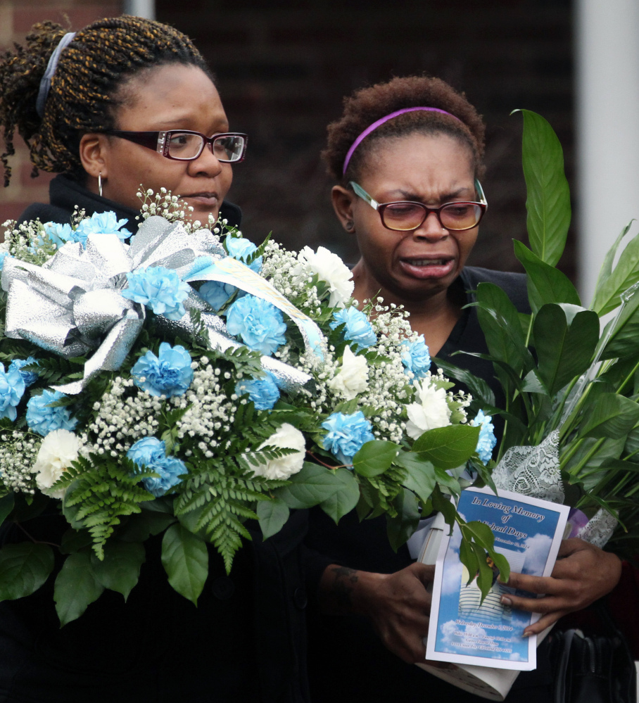 Family members cry as the body of 12-year-old Tamir Rice leaves Gaines Funeral Home on Wednesday in Cleveland. Rice was shot and killed by a Cleveland police officer late last month. Police said the rookie officer who shot Rice believed the replica gun he waved was a real firearm.