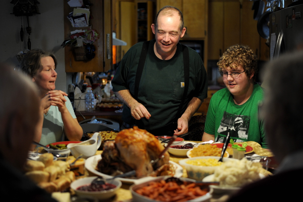 Scott Greaney prepares to carve the family bird as his wife Tracey, left, and son Ben, 15, right, watch during Thanksgiving dinner at the family's home in Mercer.