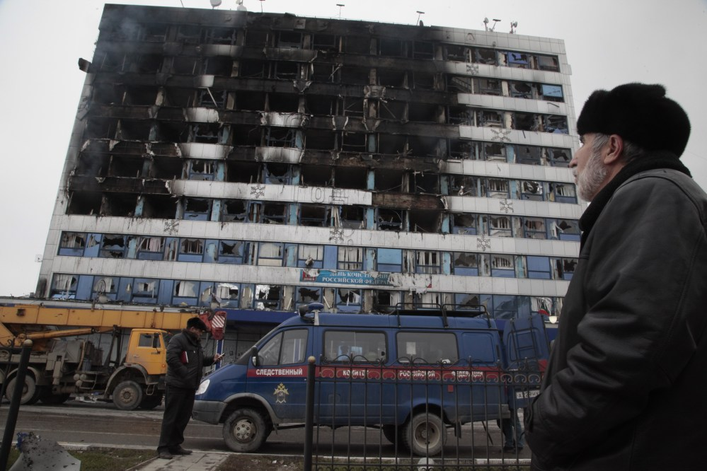 A police minivan is parked outside the burned publishing house in Grozny, Chechnya, on Thursday, where a gun battle broke out just hours before Russian President Vladimir Putin gave his annual state of the nation address in Moscow.