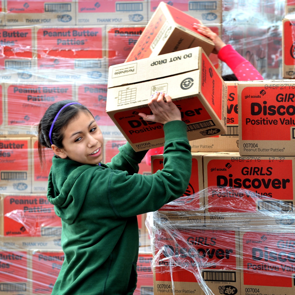 Paola Garcia stacks Girl Scout cookie boxes in Modesto, Calif. The scouts now allow online sales, but there are concerns about security issues and Internet use.