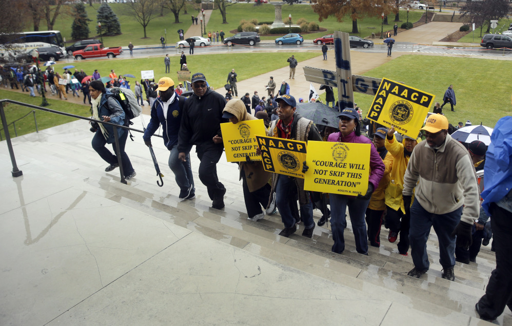 Marchers walk up the steps of the Missouri Capitol as they complete a 7-day march Friday, Dec. 5, 2014, in Jefferson City, Mo. Scores of people protesting the police shooting of Michael Brown finished the 130-mile march from the shooting site in the St. Louis suburb of Ferguson.