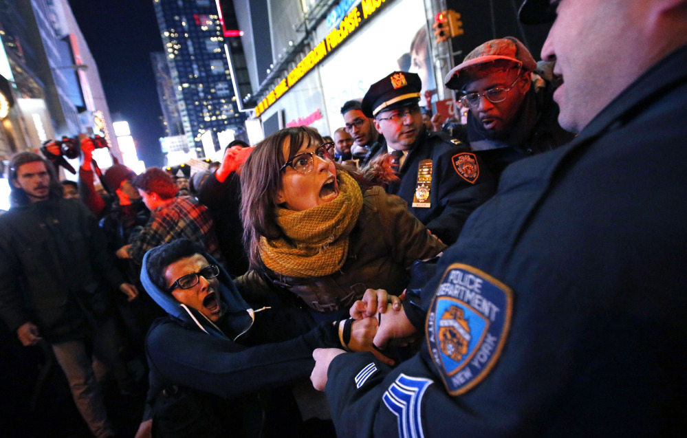 """Police arrest protesters attempting to block traffic near Times Square in New York this week after a grand jury decided not to indict the police officer involved in the death of Eric Garner. """"Police officers feel like they are being thrown under the bus,"""" said Patrick Lynch, president of the police union."""
