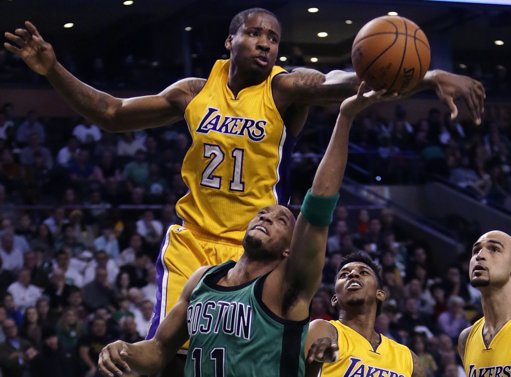 Los Angeles Lakers forward Ed Davis blocks a shot by Boston Celtics guard Evan Turner during first-quarter action of Friday night's game in Boston, won by the Celtics.