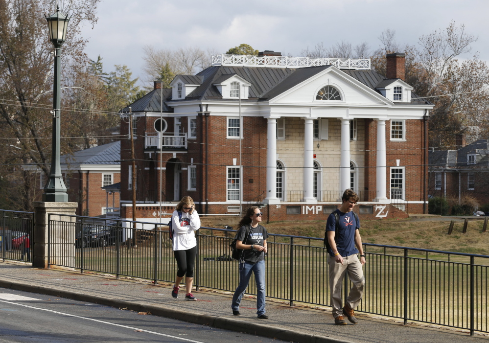 University of Virginia students walk to campus past the Phi Kappa Psi fraternity house at the University of Virginia in Charlottesville last month. Rolling Stone is casting doubt on the account it published of a young woman who says she was gang-raped at a Phi Kappa Psi fraternity party at the school, saying there now appear to be discrepancies in the student's account.