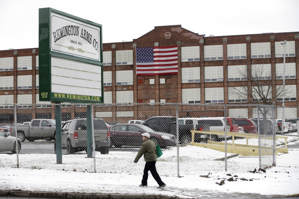 A man walks past the Remington Arms Company in Ilion, N.Y. A Manhattan father who lost his son in a rifle accident 14 years ago says he can finally rest after fighting gun manufacturer Remington Arms Co. over the triggers on its bolt-action hunting rifles. Richard Barber says that the company's action could save many Remington rifle owners from harm or death.