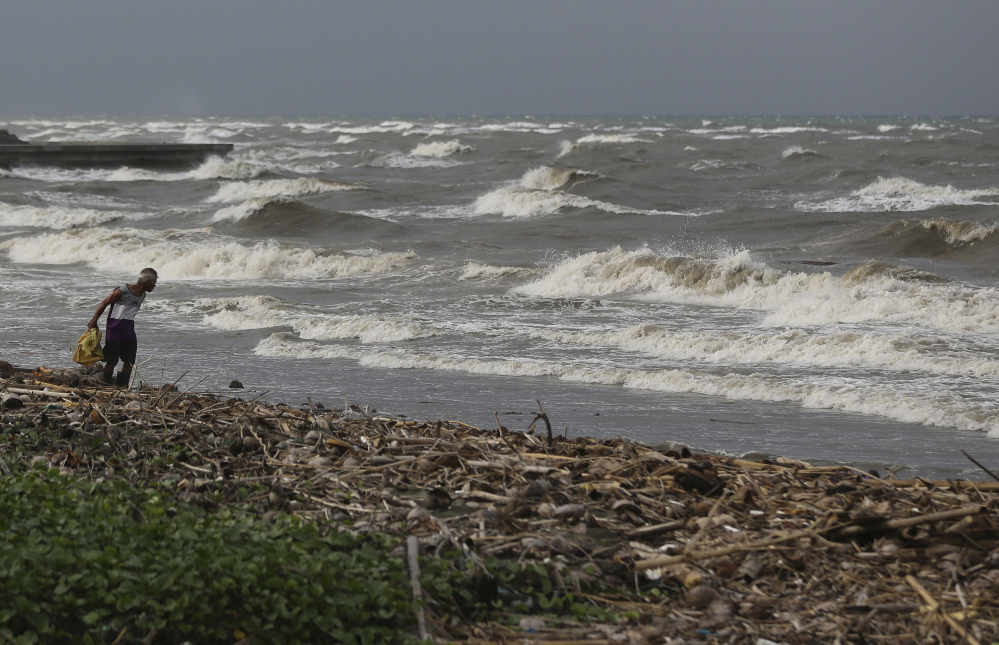A man walks along the shore as strong waves from Typhoon Hagupit hit Atimonan in the eastern Philippines on Saturday. Forecasters say Typhoon Hagupit's sustained winds and gusts are strong enough to set off deadly storm surges and landslides and cause heavy damage.