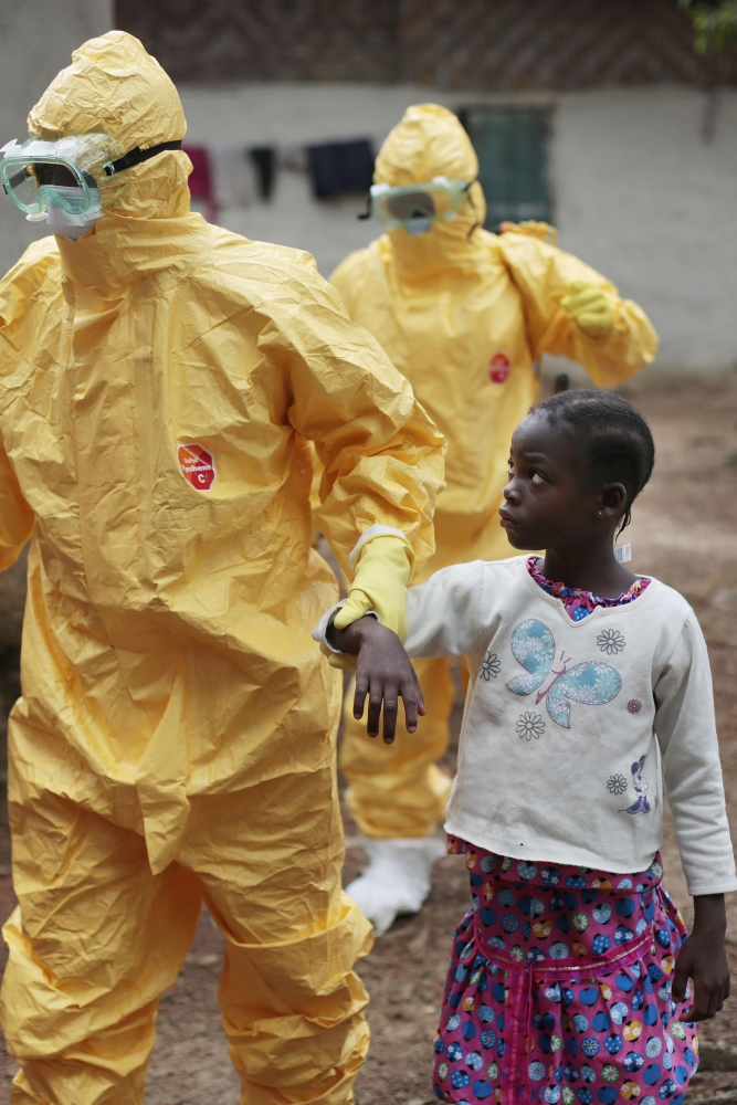 Health care workers escort a 9-year-old who showed symptoms of Ebola. Two doctors in Sierra Leone died from the virus Friday. Health care workers are among the most at risk of contracting the disease..