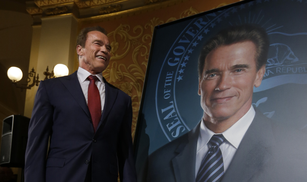 Arnold Schwarzenegger stands next to his official portrait, which used to feature a smudge that has now been fixed.