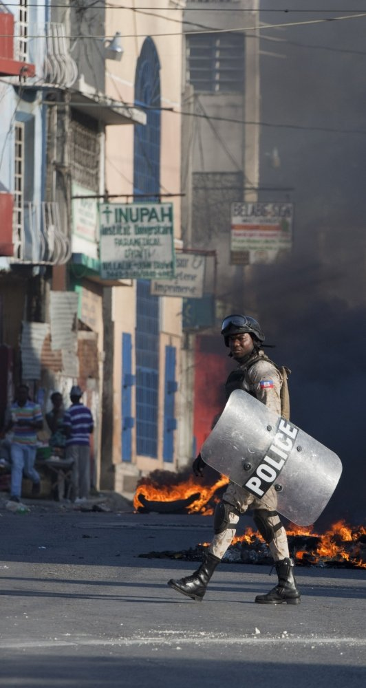 A police officer is framed by burning debris in Port-au-Prince, Haiti, on Saturday.