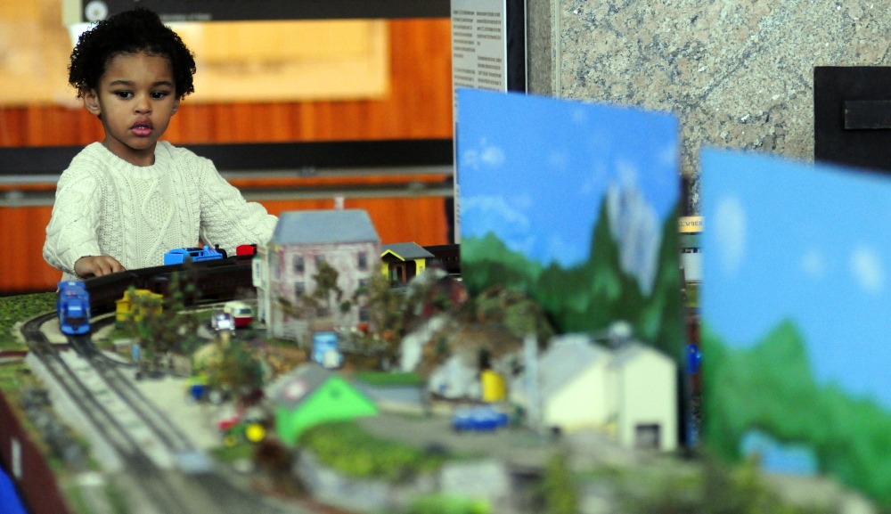 Taj Hassouna intently watches a chugging train during the Maine State Museum's annual model railroading event at the Maine State Cultural Building in Augusta on Saturday.