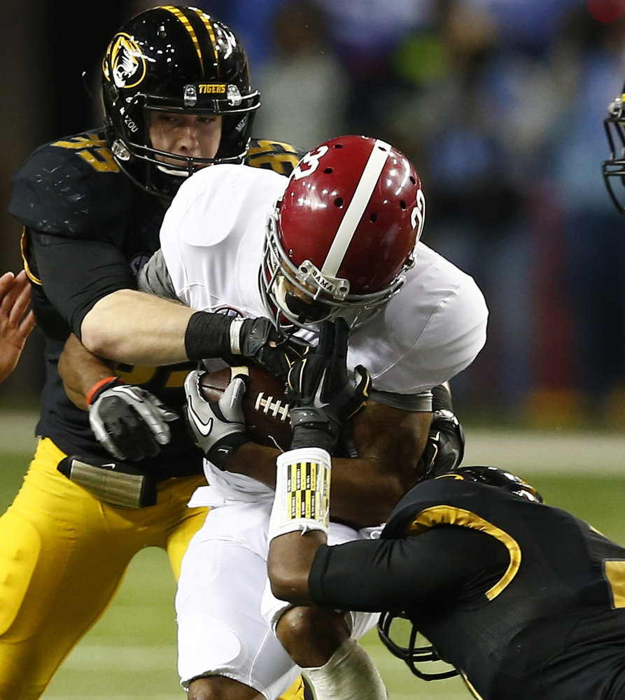 Alabama wide receiver Christion Jones, 22, runs into Missouri defensive lineman Marcus Loud, 35, as safety Ian Simon holds on during the second half of the SEC championship game Saturday in Atlanta.