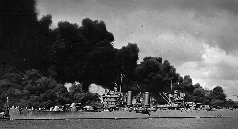 The USS Phoenix, the ship Watson was serving on as a gunner's mate first class, sails past the burning USS Arizona and USS West Virginia in Pearl Harbor after Japan attacked on Dec. 7, 1941.