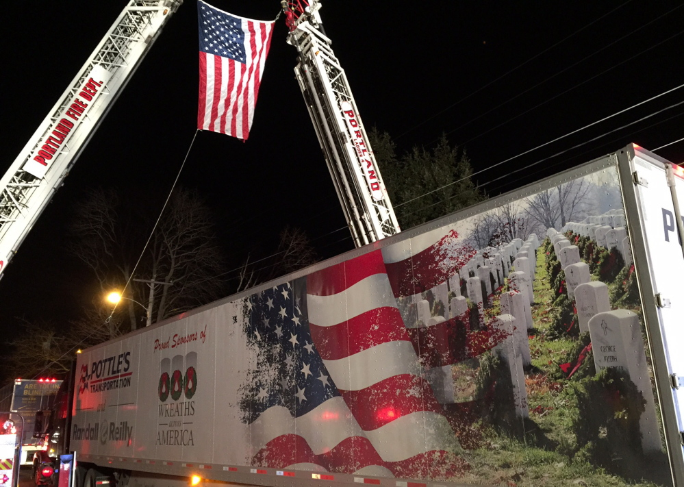A tractor-trailer filled with balsam wreaths passes under an American flag outside Cheverus High School in Portland on Sunday.