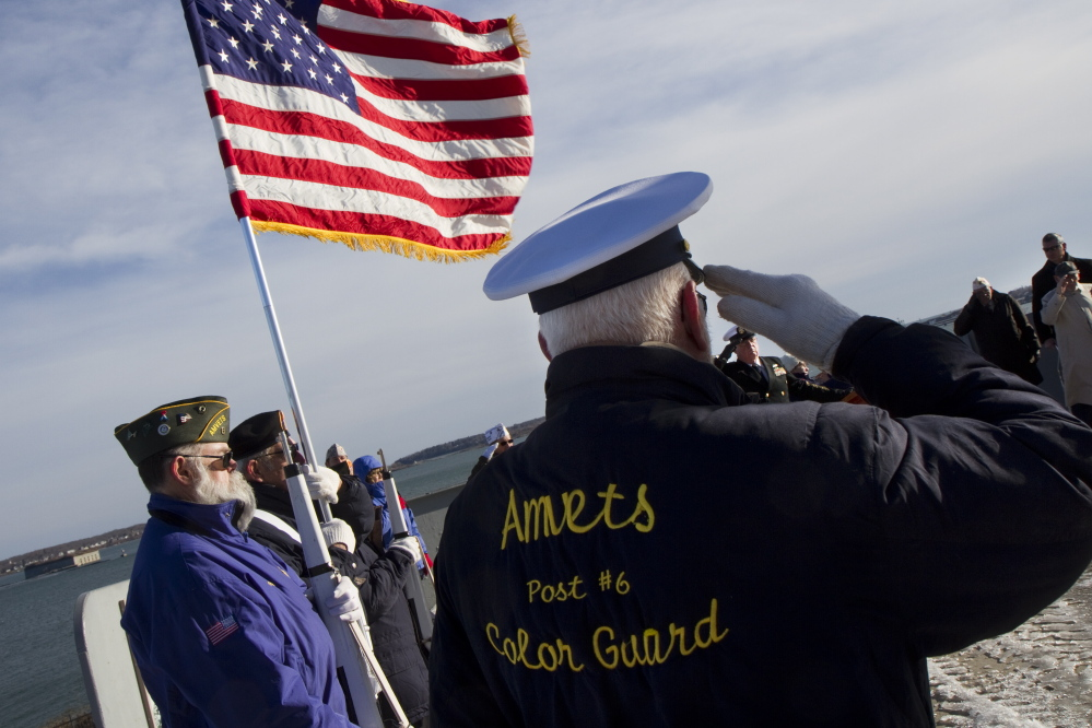 Wes Rogers salutes while standing with fellow members of the AMVETS Post 6 Color Guard during a commemoration ceremony at Fort Allen Park in Portland on Sunday, the anniversary of the Pearl Harbor bombing.