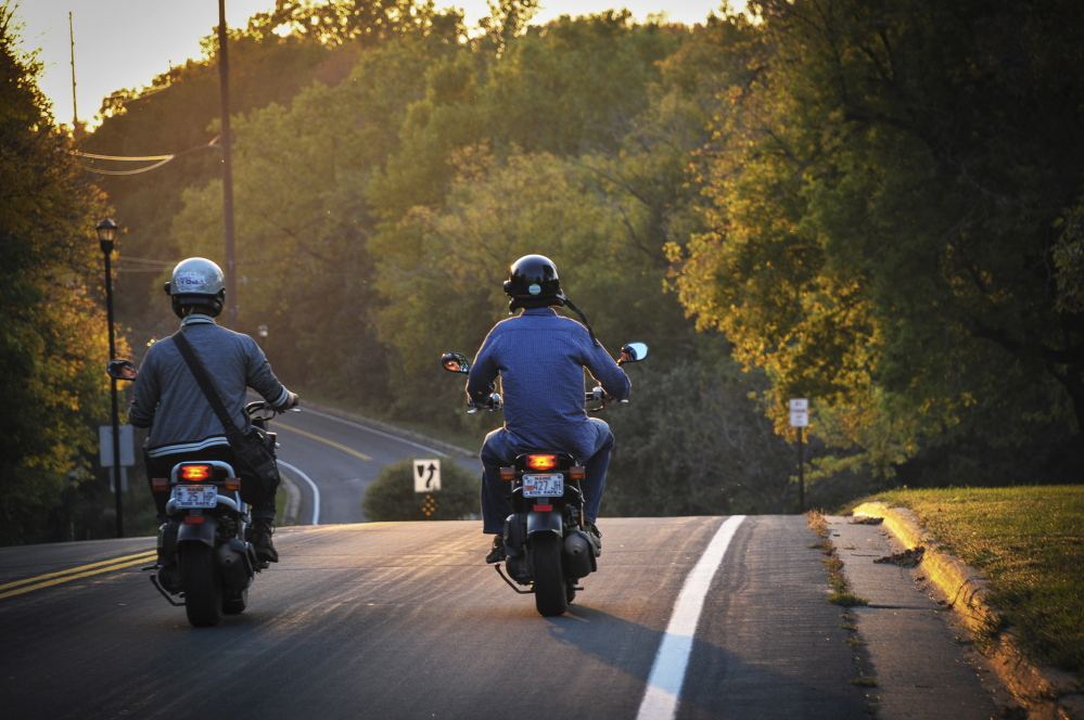 Myles Chung, left, and Dan Emery drive their scooters through Missouri.