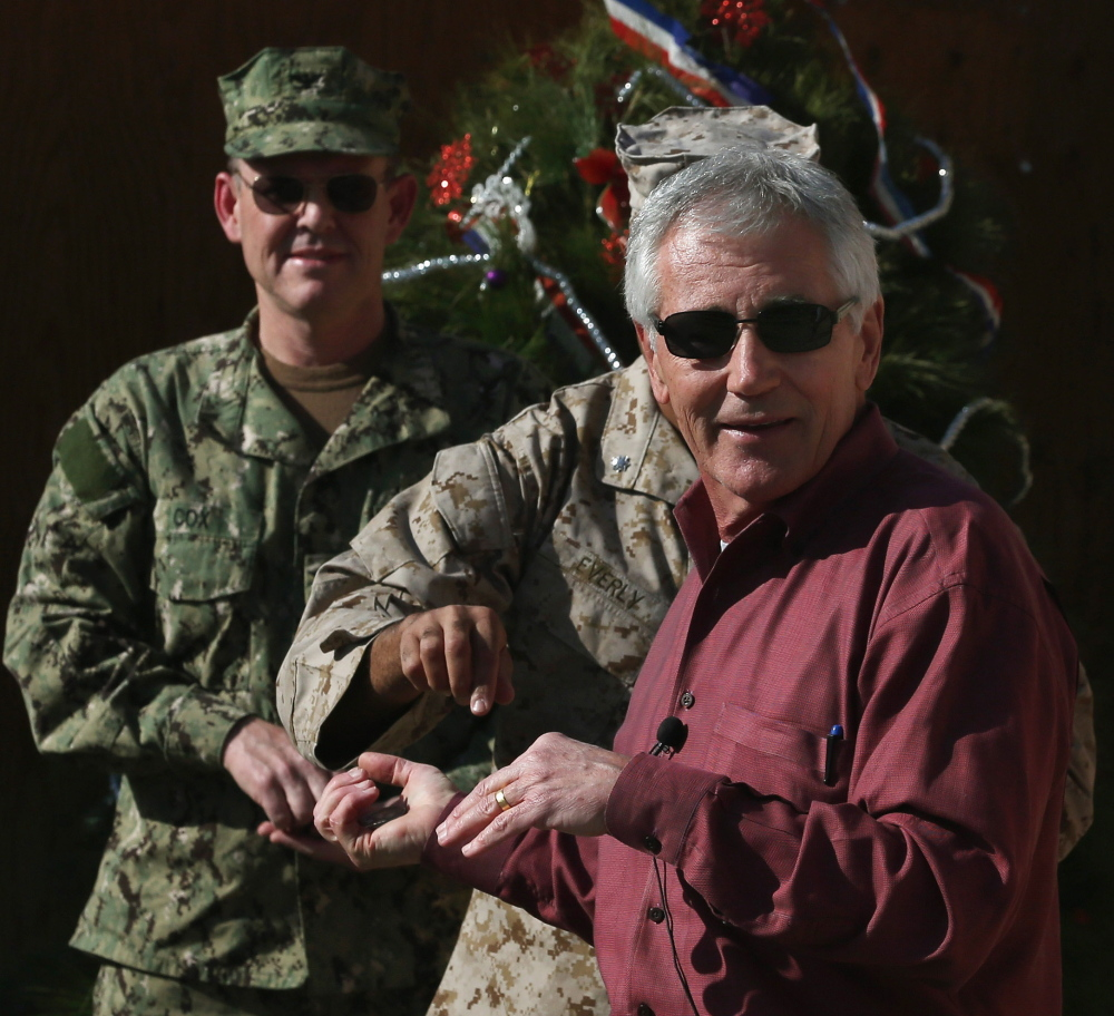 """U.S. Secretary of Defense Chuck Hagel, right, said """"we don't want to see the ball roll downhill"""" as the U.S. reduces its presence in Afghanistan."""