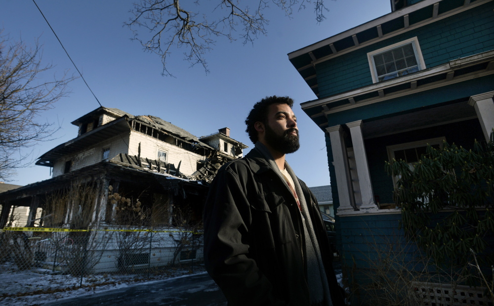 """Zach Darwin, standing in front his Noyes Street apartment building, says the charred building next door is a constant reminder of the tragedy of Nov. 1, when six young adults died in a fire there. """"It hurts to see this every day. My girlfriend and I are moving out,"""" he said."""