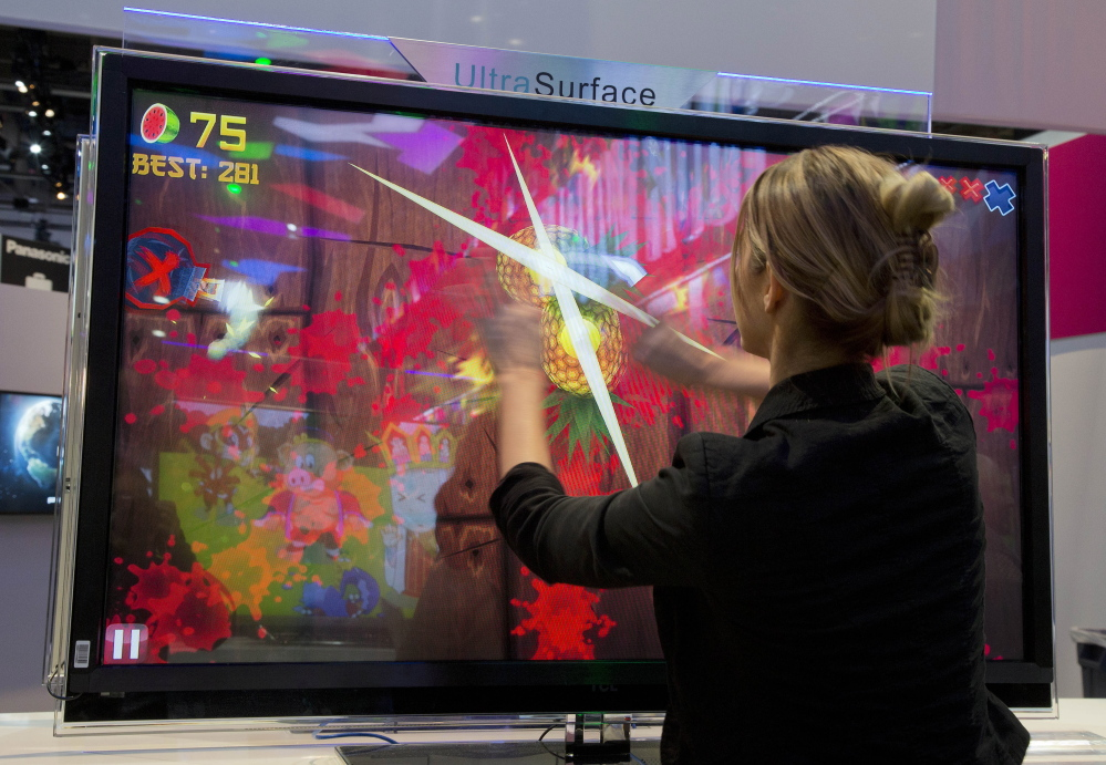 An attendee plays Fruit Ninja at the Panasonic booth at the 2013 Consumer Electronics Show in Las Vegas. More than a year after federal regulators issued new privacy rules for kids' mobile apps, online stores remain flooded with cute and silly software programs that quietly collect vast amounts of data on the youngest consumers.