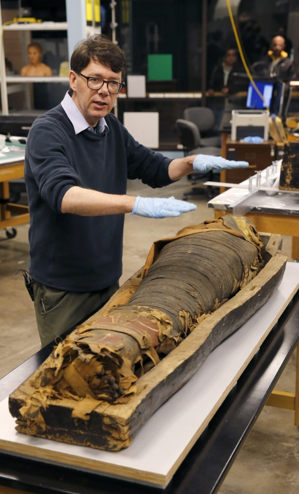 P.J. Brown stands over the mummified body of Minirdis, a 14-year-old Egyptian boy. Brown says his museum will fix Minirdis' burial mask and reconnect his detached feet.