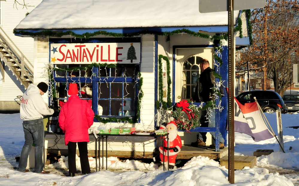 Santa's helpers C.J. Duplessie, left, and Tina Worthley set out treats and hot coffee outside Santaville on Main Street in Madison.
