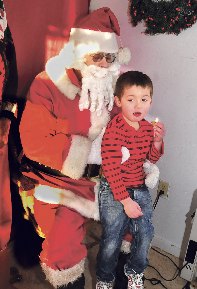 Between cookie bites, 3-year-old Sebastion Christie tells Stephen Foshay, dressed as Santa, what he wants for Christmas .