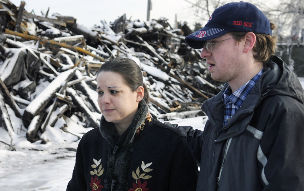 Jennifer Hogan and James Wiggin search Monday around the rubble of their former apartment building in Augusta for their cats. The animals disappeared during the blaze last week that destroyed their home.