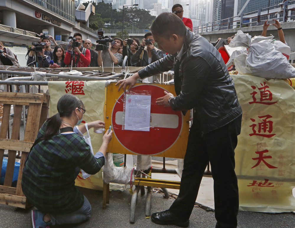 Hong Kong authorities post an injunction document on a barricade set up by pro-democracy protesters at the occupied area outside government headquarters Tuesday.