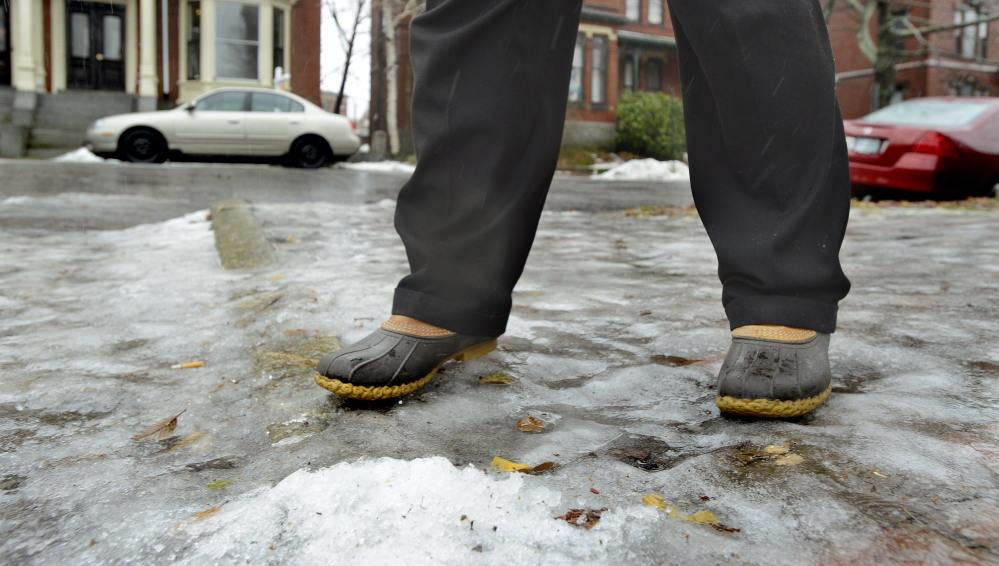 """Herb Adams of Portland makes his way along Deering Street on Wednesday as he and other pedestrians tried to negotiate the city's icy sidewalks and streets. """"People ... were falling,"""" he said. """"If you were near enough, you'd slide over and help them up and hope that you would make it."""""""