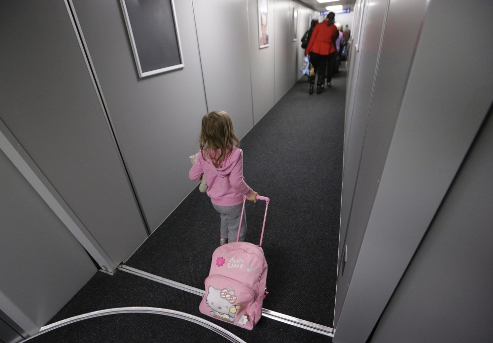 Symphony Rader, 4, pulls a bag down the boarding ramp last month at Love Field in Dallas. The first flight of the day sets the tone for keeping flights running on time.