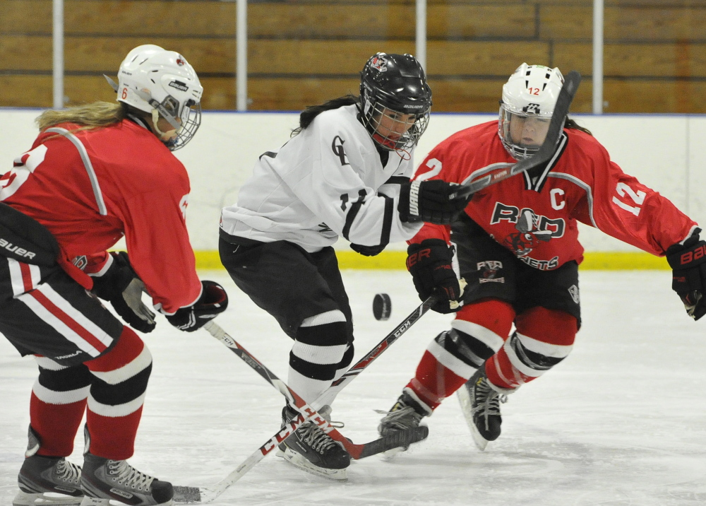 Kathryn Clark, center, of Cape Elizabeth/Waynflete fights for the puck between Edward Little/Leavitt/Poland's Haley Frohlich, left, and Danica Nadeau during a 5-3 win against Cape Elizabeth/Waynflete Wednesday afternoon.