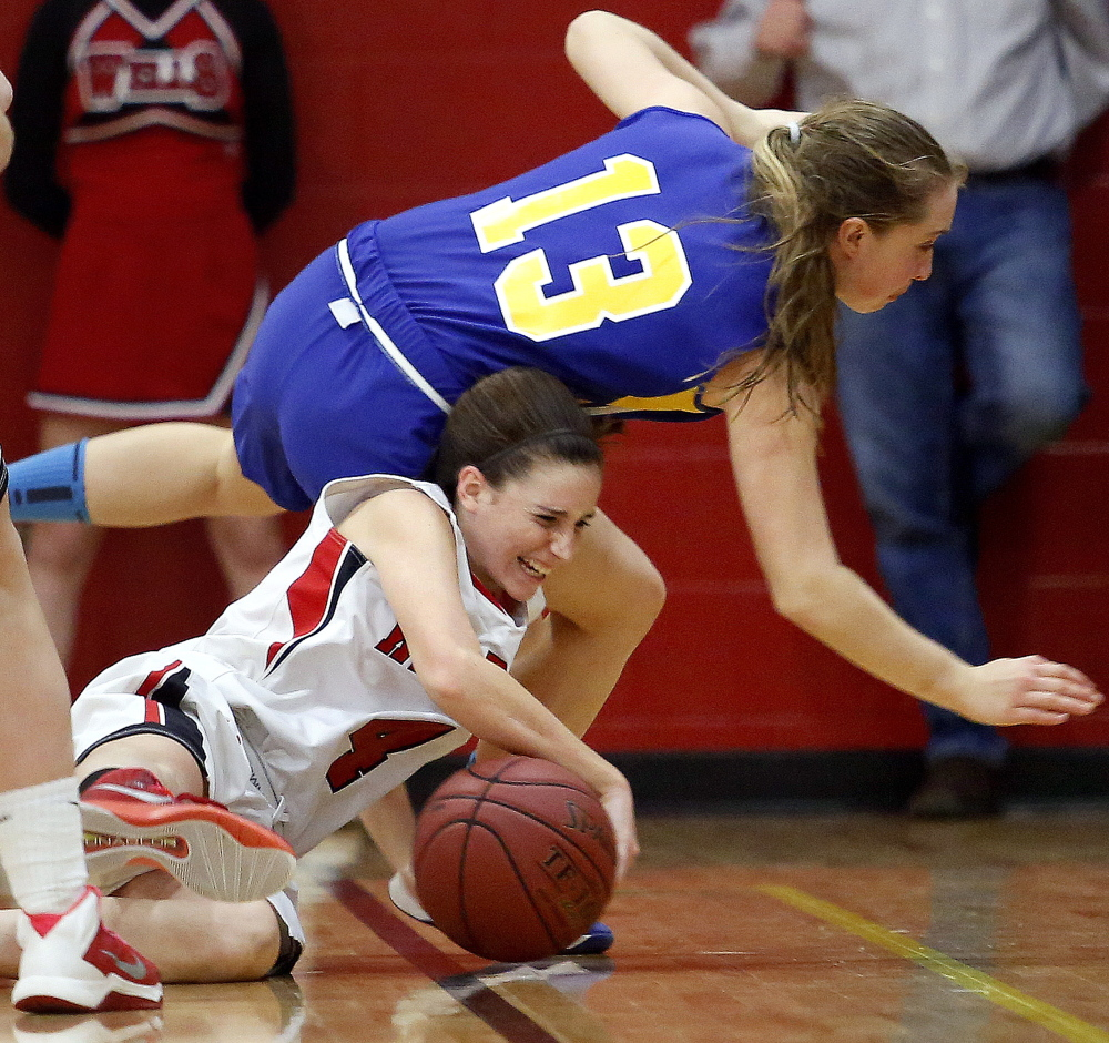 Natalie Thurber of Wells tries to protect the ball as she and Maddy Adams of Falmouth fall to the floor during Thursday's game.