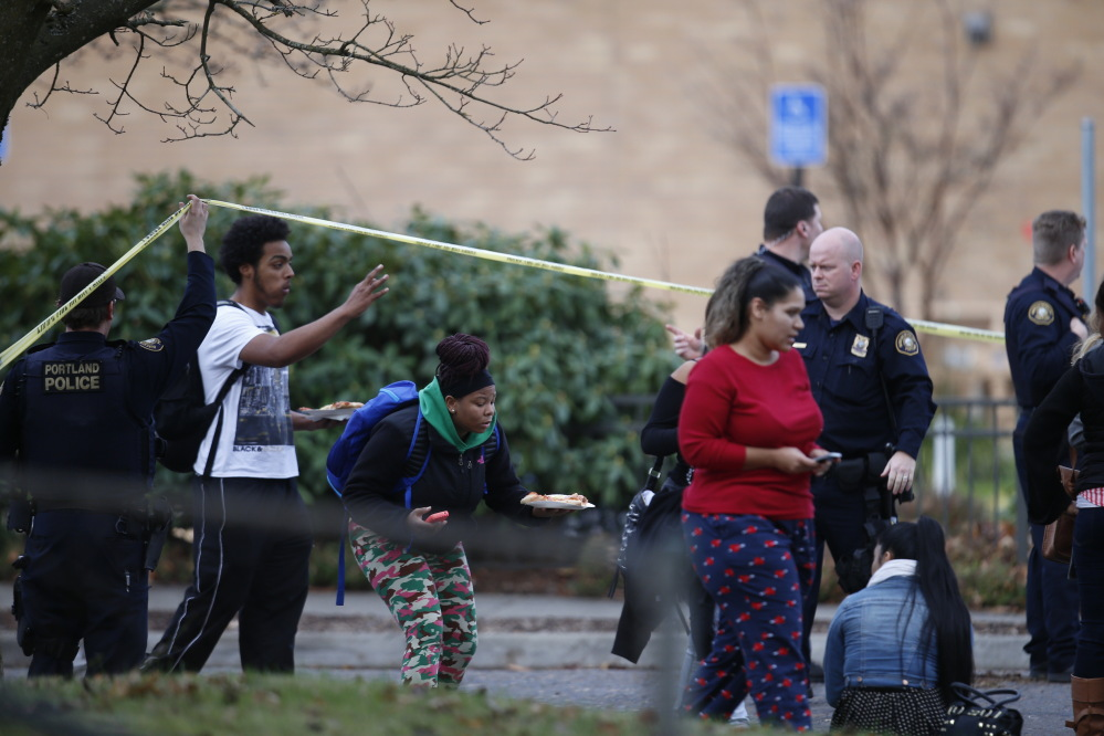 Officials direct youth at the scene of a shooting at Rosemary Anderson High School in Portland, Oregon, on Friday.