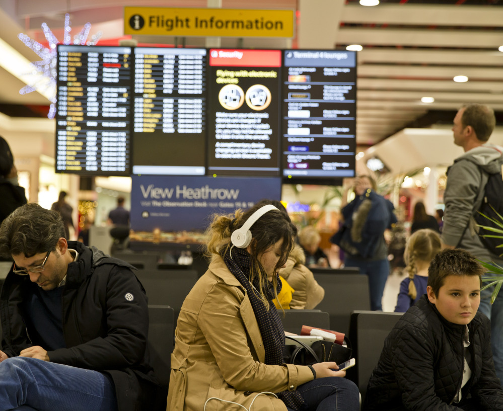 Passengers wait for flights to take off at Heathrow Airport in London after the city's airspace was closed for a time on Friday because of a computer failure.