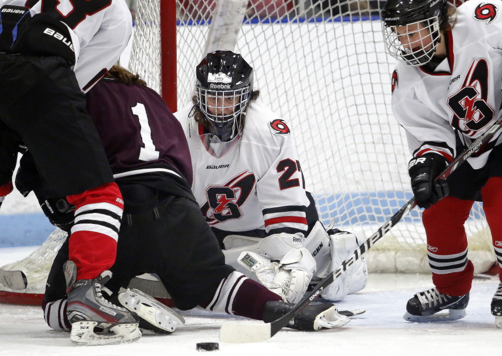 Scarborough goalie Lucca Sterrer keeps her eyes on the puck as teammate Lily Nygren, right, prepares to clear it Saturday during a game against Greely at MHG Ice Centre in Saco. Greely won 4-2.