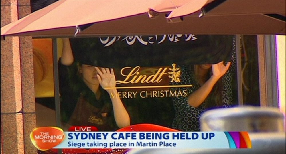 This image taken from video shows people holding up what appeared to be a black flag with white Arabic writing on it, inside a cafe in Sydney, Australia Monday.