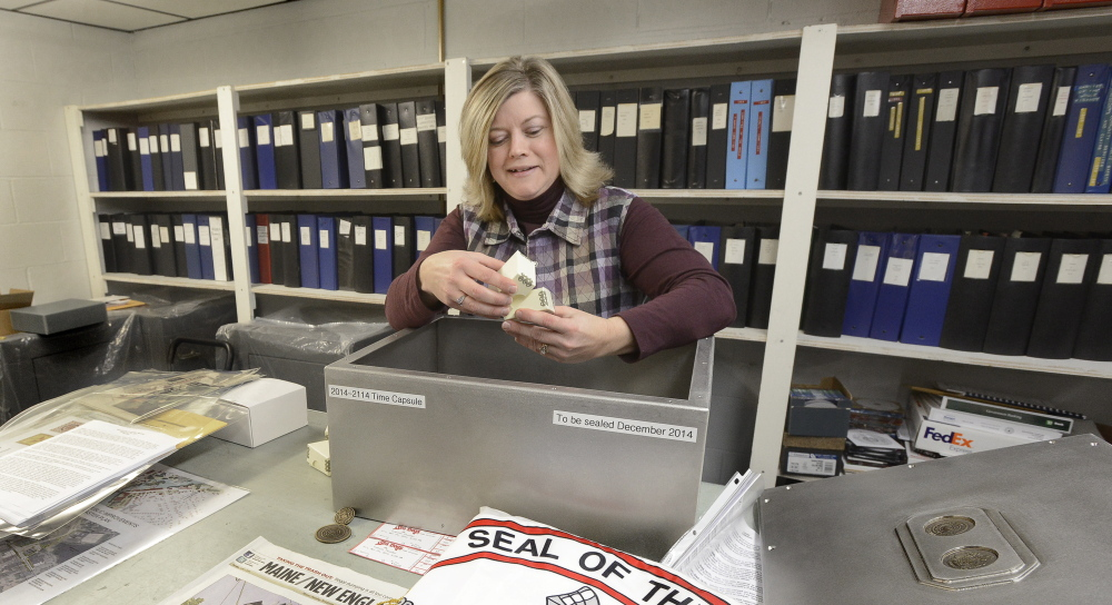 Westbrook City Clerk Lynda Adams shows some of the non-secret items to be placed in a new time capsule, which will be sealed Tuesday. The city's Bicentennial Committee hopes the secrecy will build excitement before the box is opened.