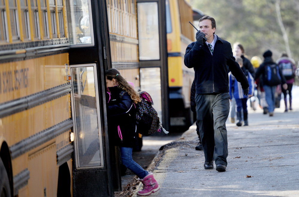 Windham Primary School Principal Kyle Rhoads talks on a radio as students board buses Monday,
