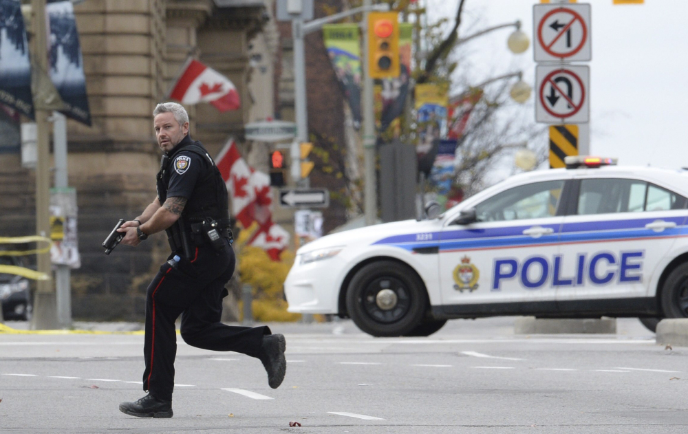 An Ottawa police officer runs with his weapon drawn outside Parliament Hill on Oct. 22. Radical Muslim Michael Zehaf-Bibeau's killing of a soldier at a war memorial outside Canada's parliament is one of many attacks by solo terrorists.