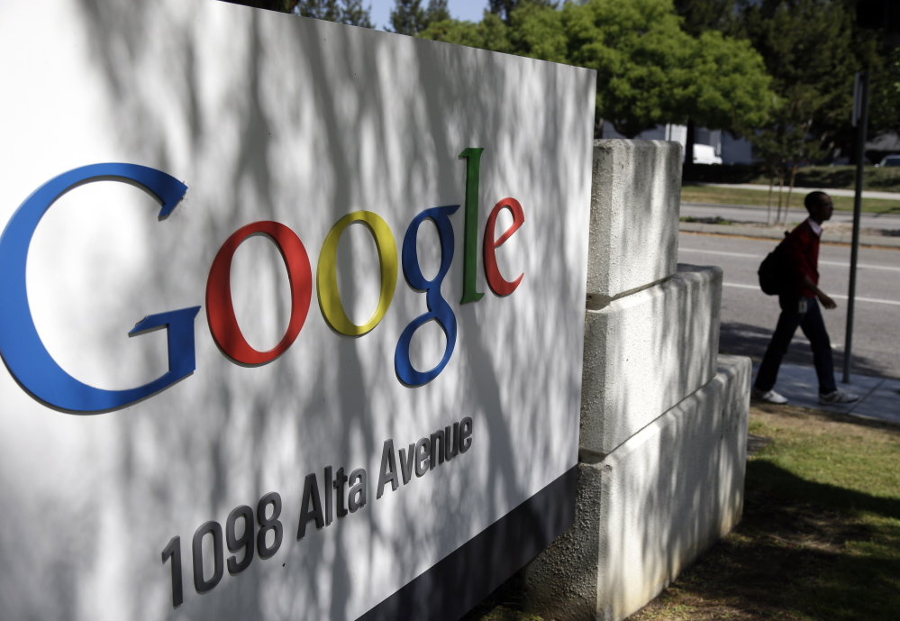 A man walks past a Google sign at the company's headquarters in Mountain View, Calif.  Google is one of the major U.S. corporations researching the power of color in the working world, in everything from workspaces to marketing and branding.