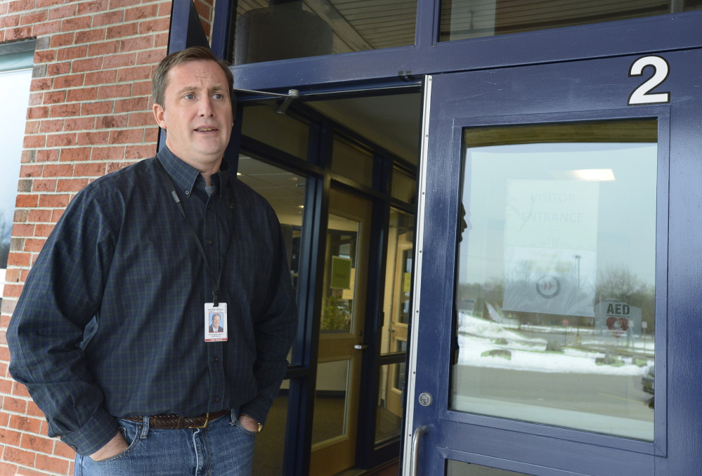 Windham High School Principal Christopher Howell speaks briefly Tuesday outside the locked school doors. He and the custodial staff were the only people in the building, he said.