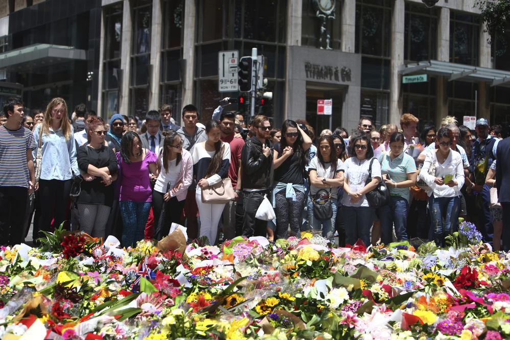 Staff members from the Lindt Chocolat Cafe with their arms linked pay tribute to their colleague who lost his live during a siege at the popular coffee shop at Martin Place in the central business district of Sydney, Australia, Tuesday.