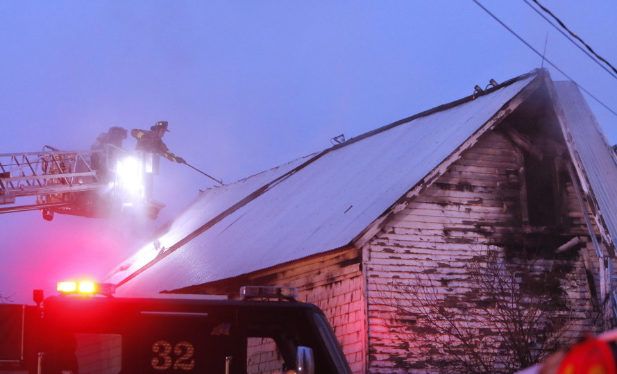 A Biddeford firefighter vents the roof of a home at 25 River Road in Biddeford on Tuesday.