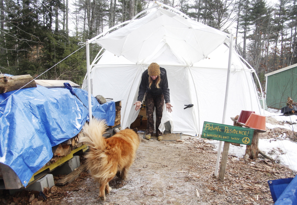 Kate Wentworth, 26, greets her dog, Bruiser, an 8-year-old chow/Australian shepherd cross, at the door of her yurt. She is living on a homestead in York County for the winter in an attempt to experience the way her ancestors lived.