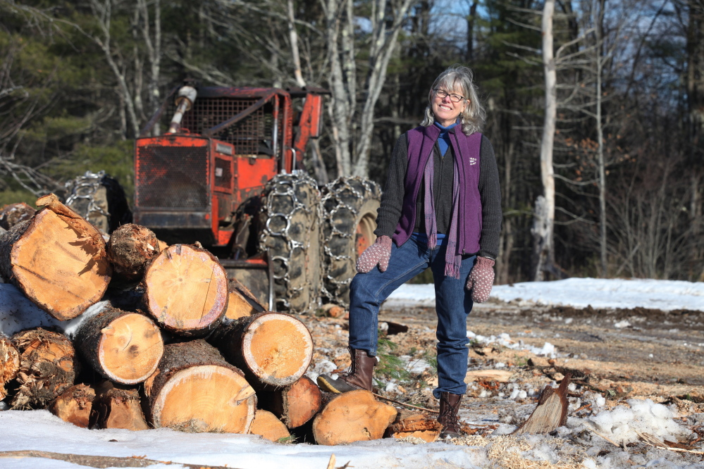 LEEDS, ME - DECEMBER 19: Theresa Kerchner, executive director of the Kennebec Land Trust poses in front of a skidder Friday, Dec. 19, 2014 at Curtis Homestead in Leeds, Maine. The conservation area has hiking trails along with having a sustainable forestry education program. Photo by)