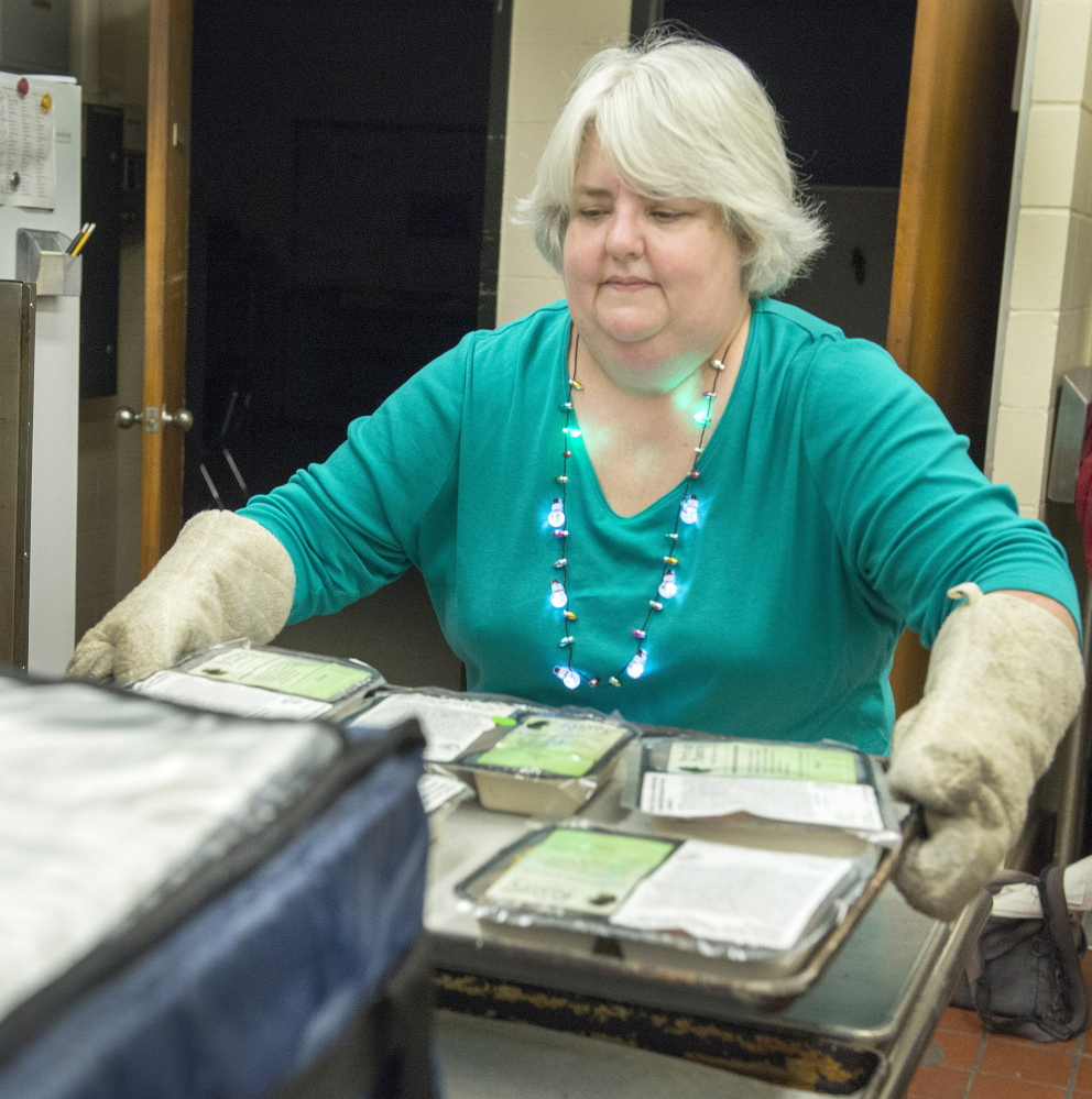 Beth Miller of Portland takes heated dinners out of the oven.