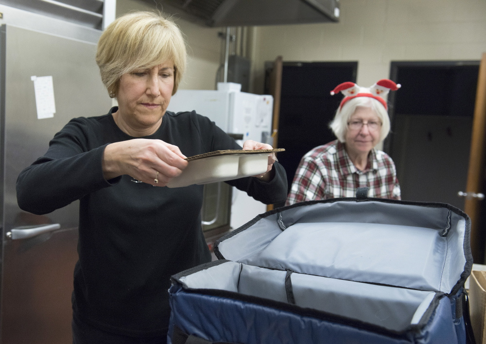 Volunteer Jackie Harkins of Portland puts a hot meal into an insulated carrying bag for delivery to a homebound senior on Christmas Day. Staff from the Southern Maine Agency on Aging and volunteers from the Portland Rotary Club joined in the holiday spirit of giving. At right is Deb Welton.