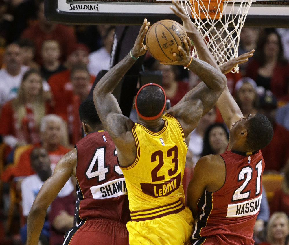 LeBron James of the Cleveland Cavaliers heads to the rim between Shawne Williams, left, and Hassan Whiteside of the Miami Heat during the first half of Miami's 101-91 victory.