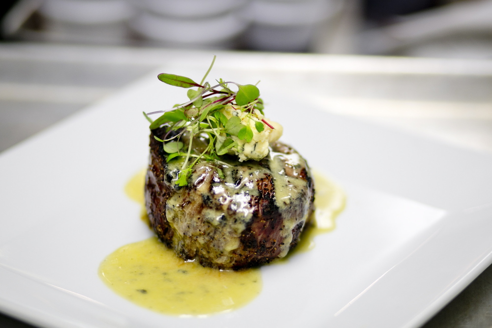 The filet mignon is adorned simply with a scoop of Stilton and a smattering of greens.